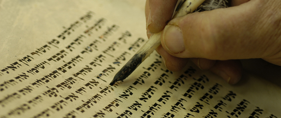 Scribe writing Hebrew text.